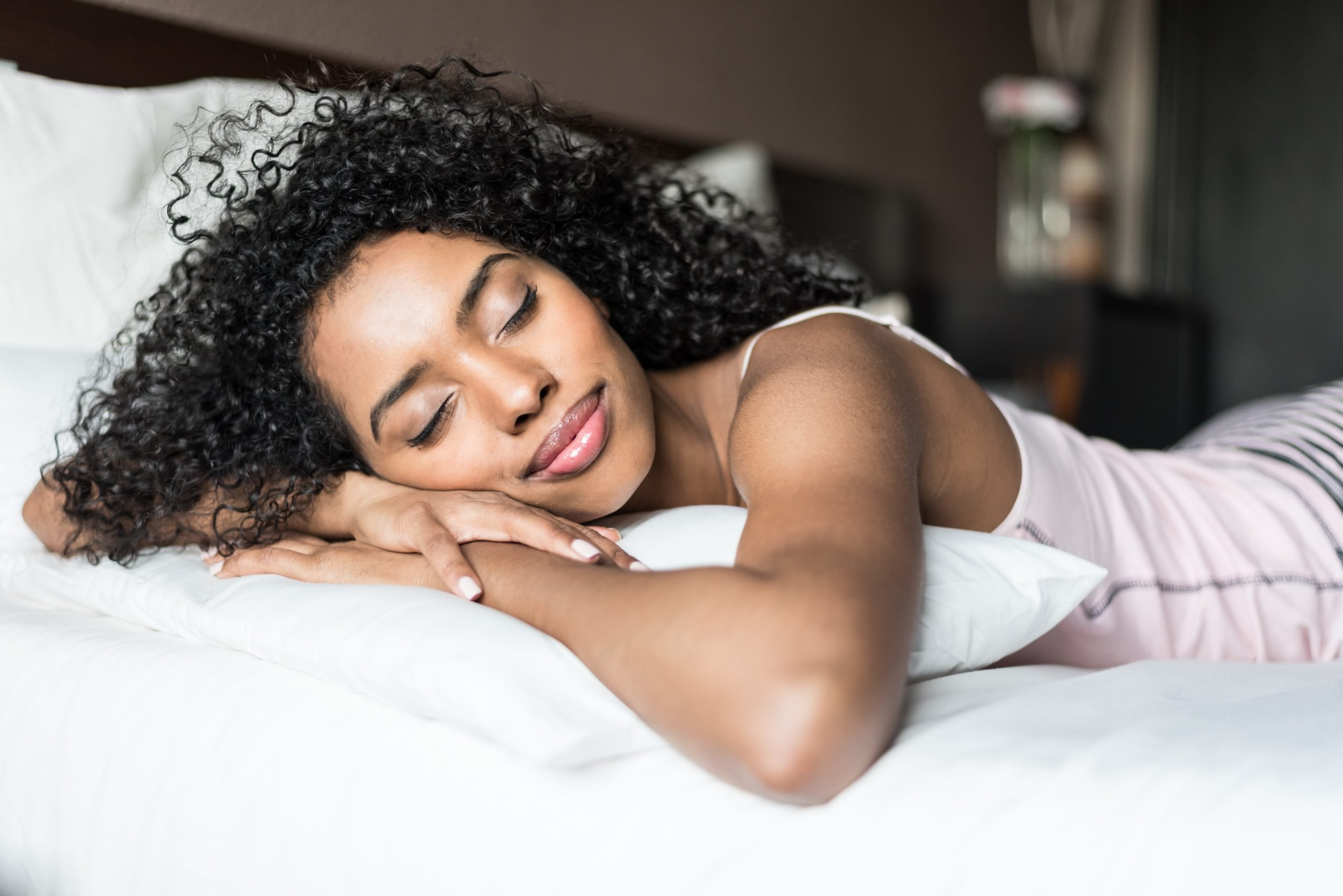 young african american woman sleeping on her hands in bed